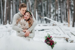 Bride and groom are hugging in the winter forest. Close-up. Winter wedding ceremony.
