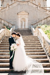 bride and groom are hugging on the stairs of the Nativity of the Blessed Virgin Mary church in Prcanj