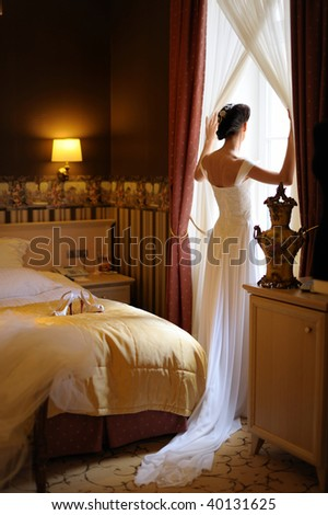 Bride and groom are standing against the window looking outside