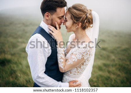 Bride and groom are standing face to face with the green hills on background #1118102357
