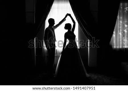 Bride and groom at the window. Silhouette of the bride and groom at the window. Silhouette of newlyweds. Newlyweds at the window. Dance of the newlyweds. The bride and groom waltz. Wedding dance