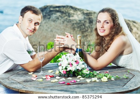 stock photo Bride and groom at wedding table near the sea