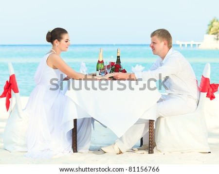 stock photo Bride and groom at wedding table on the beach