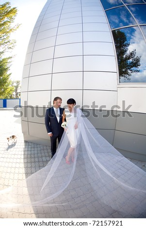 bride and groom by the wall with long flying veil