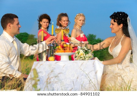 stock photo Bride and groom clinking glasses of champagne at wedding table