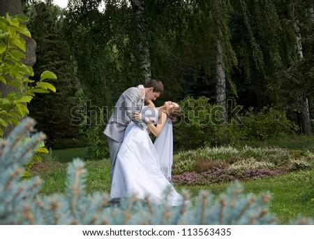 Bride and groom dancing in a park - outdoor
