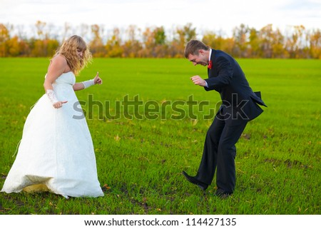 bride and groom dancing merrily in green field, couple, wedding fall