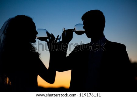 Bride and groom drink wine at sunset
