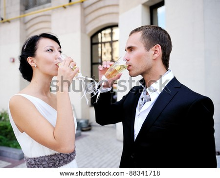 Bride and groom drinking champagne outdoor after a wedding ceremony