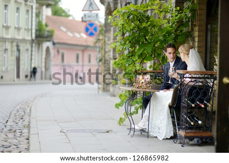 Bride and groom drinking wine at an outdoor cafe