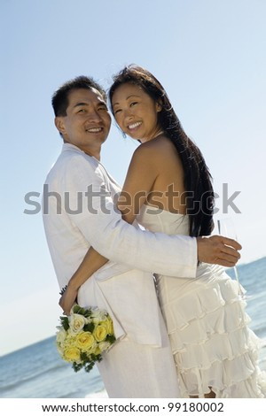 Bride and Groom Embaracing on Beach
