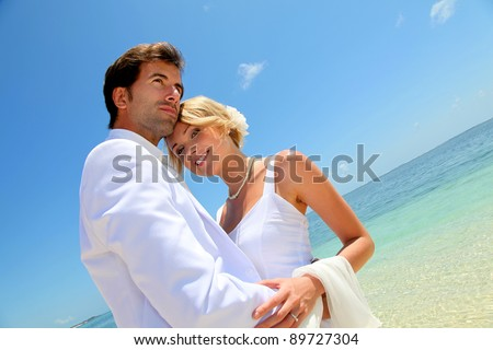 Bride and groom embracing by the sea