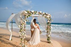 Bride and groom enjoying beach wedding in tropics,  wedding arch, ocean background