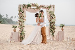 Bride and groom enjoying beach wedding in tropics, wedding arch, ocean background. Wedding ceremony on a tropical beach. Happy groom and beautiful bride kissing under the arch decorated with flowers
