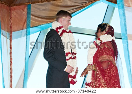 Bride and groom exchange garlands during a traditional hindu ceremony