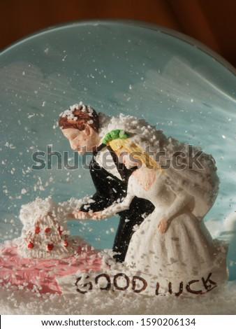 Bride and groom figurines in snow globe