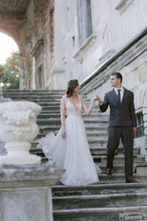 Bride and groom going down by stairs in old palace and looking at each other. Wedding couple. Wedding photo. High quality photo