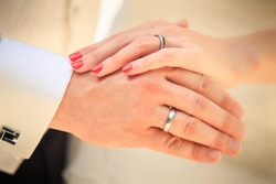 bride and groom hands with golden rings clouseup