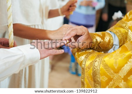 Bride and groom hands with ring during orthodox church wedding ceremony
