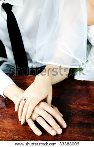 Bride and groom hands with rings on wooden table