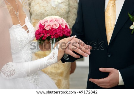 stock photo Bride And Groom Hands with Wedding Rings and Flowers Bouquet
