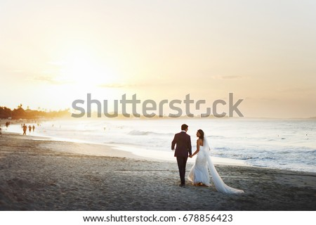 Bride and groom hold each other hands posing on the beach