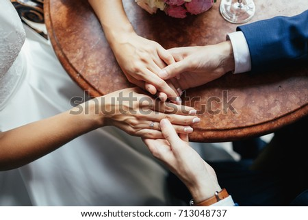 Bride and groom hold each other hands tender