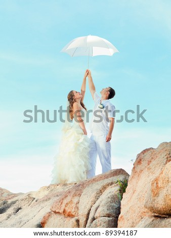 Bride and groom holding an umbrella on a rock. - stock photo