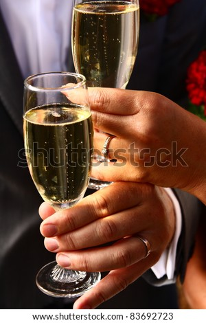 Bride and groom holding champagne glasses and toasting - stock photo