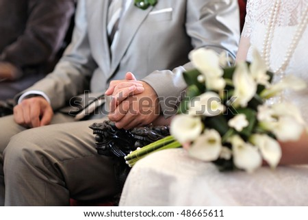 Bride and groom holding each others hands during wedding ceremony