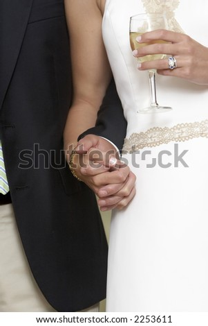 Bride and groom holding hands and a glass of white whine