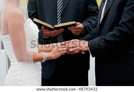 bride and groom holding hands during ring exchange part of an outdoor wedding ceremony