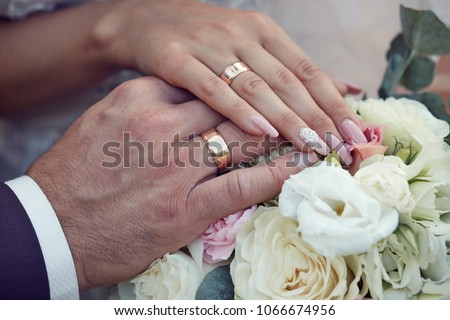 bride and groom holding hands on a wedding bouquet of roses #1066674956