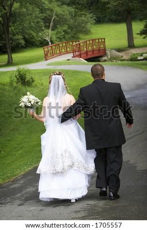 Groom holding hands walking away
