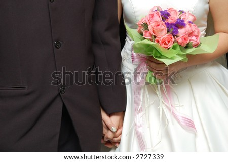 bride and groom holding hands with bouquet of pink roses