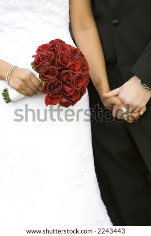 bride and groom holding hands with bouquet of red roses