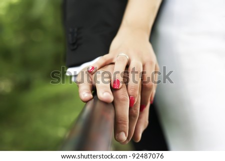 stock photo Bride and groom holding hands with wedding rings