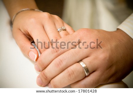 bride and groom holding hands with wedding rings on it - stock photo
