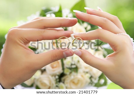 Bride and groom holding two rings over wedding bouquet