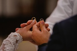 Bride and groom holding up their alliances, along with the hand of the priest. On the day of the wedding, the ring, the bride and the groom's ring on his hand