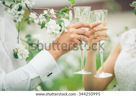 Bride and groom holding wedding champagne glasses #344250995