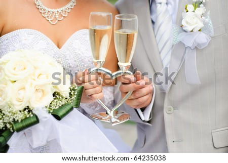 Bride and groom holding wedding heart-shaped glasses with champagne