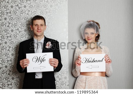 "Bride and groom holding white sheets with the text ""Mr."", ""Mrs."""