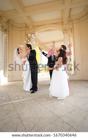 Bride and groom hugging at wedding as guests throw confetti