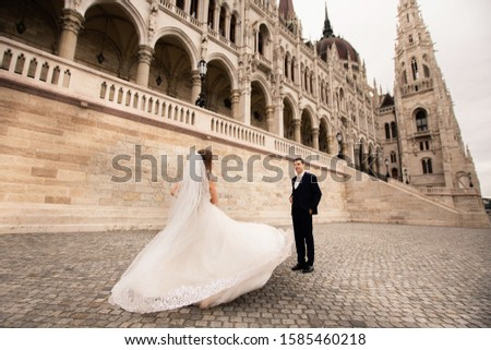 Bride and groom hugging in the old town street. Wedding couple walks in Budapest near Parliament House.