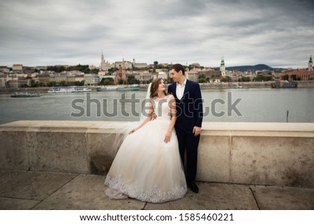 Bride and groom hugging in the old town street. Wedding couple walks in Budapest near Parliament House. Bride and groom near the river.