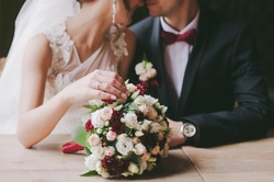 bride and groom in a cafe. wedding bouquet on a wooden table in a restaurant bride and groom hold each other's hands. Wedding rings. Loving couple in a cafe. hot tea for lovers
