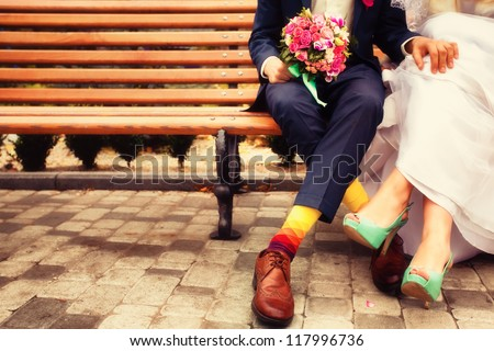 Bride and groom in bright clothes on the bench - stock photo