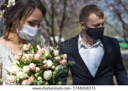 bride and groom in protective masks. Wedding during the period of quarantine and pandemic Covid 19-20, coronavirus wedding. The groom and the bride in wedding dresses, with dresses in protective masks