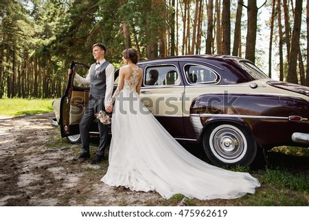 Bride and groom in the forest near luxury wedding car #475962619
